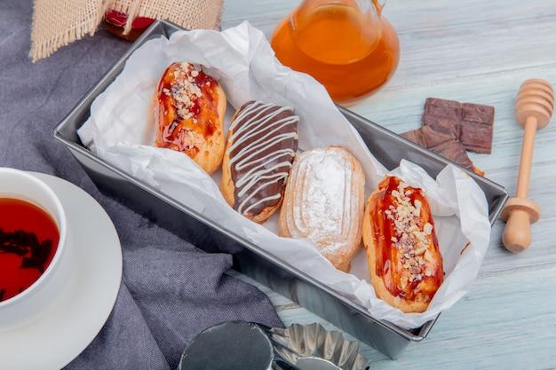 Vista laterale delle torte con la tazza di tè al cioccolato al burro intorno sul panno e sulla superficie di legno