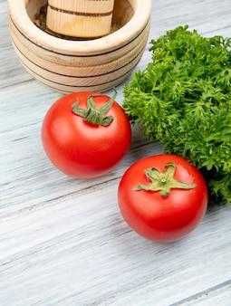Vista laterale delle verdure come coriandolo del pomodoro con il frantoio dell'aglio sulla tavola di legno