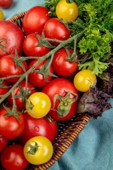 Vista laterale delle verdure come merce nel carrello del basilico del coriandolo dei pomodori sul panno blu