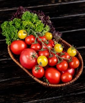 Vista laterale delle verdure come merce nel carrello del basilico del coriandolo dei pomodori sulla tavola di legno