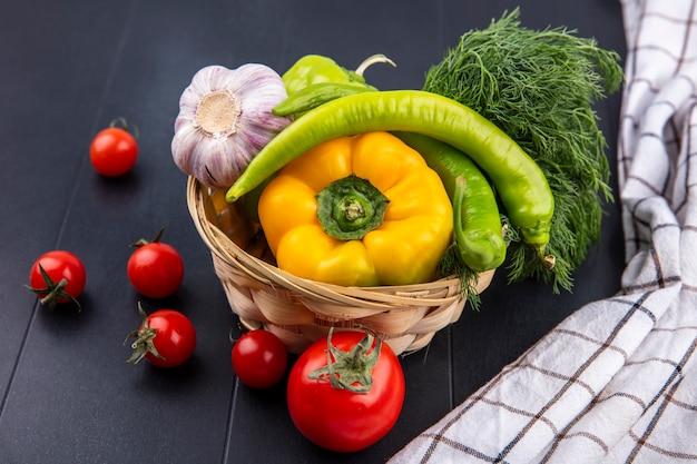 Vista laterale delle verdure come merce nel carrello dell'aneto dell'aglio del pepe con i pomodori e il panno del plaid sul nero