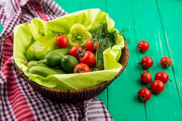 Vista laterale delle verdure come merce nel cestino dell'aneto del cetriolo del pomodoro del pepe sul panno e sul verde del plaid