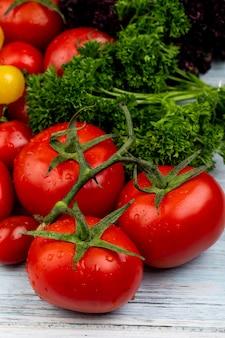 Vista laterale delle verdure come pomodori coriandolo e basilico sulla tavola di legno