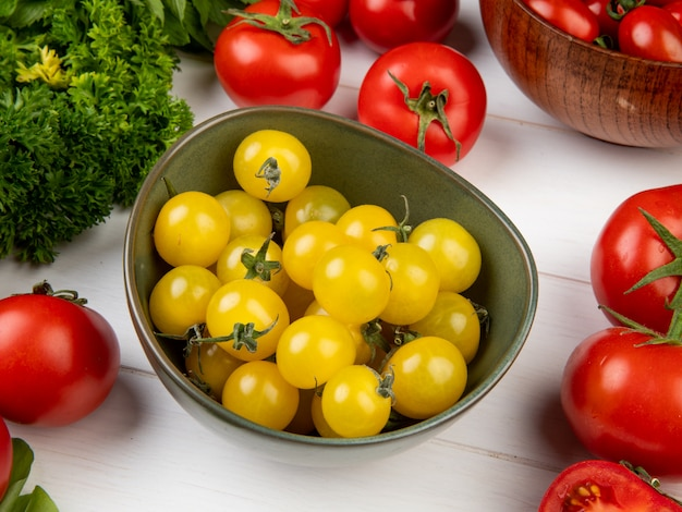 Vista laterale delle verdure come pomodoro di coriandolo con la ciotola di pomodori gialli sulla tavola di legno