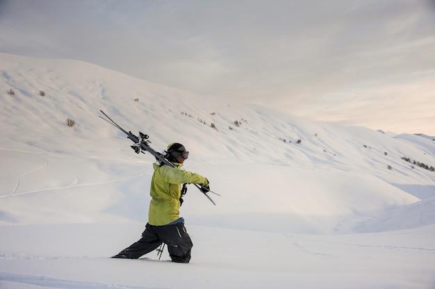 Vista laterale dello snowboarder professionista che cammina nelle montagne