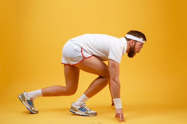 Vista laterale dello sportivo in occhiali da sole preparando a correre