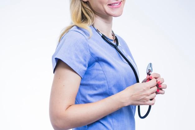 Vista laterale dello stetoscopio della holding della mano del dentista femminile