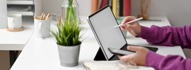Vista laterale dello studente di college femminile che fa assegnazione con la tavola, lo smartphone e la cancelleria del modello