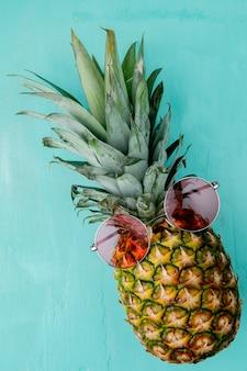 Vista laterale di ananas con gli occhiali su di esso sulla superficie blu