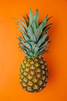 Vista laterale di ananas sulla superficie arancione