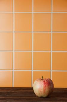 Vista laterale di apple su uno spazio di sfondo di piastrelle in legno e arancione per il testo