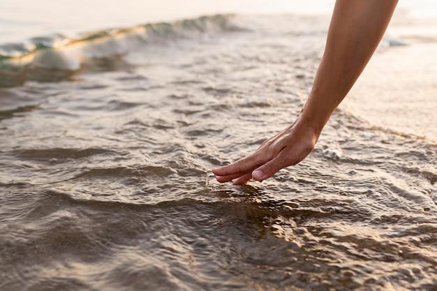 Vista laterale di aver toccato l'acqua in spiaggia