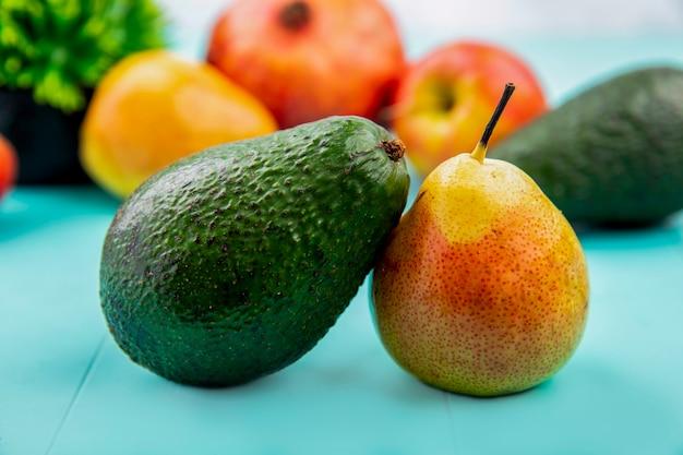 Vista laterale di avocado fresco e verde con pera sulla superficie blu