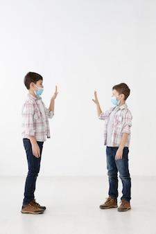 Vista laterale di bambini con maschere mediche che si salutano