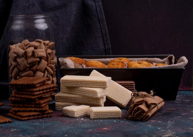 Vista laterale di biscotti al cioccolato e cialde croccanti su oscurità