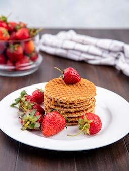 Vista laterale di biscotti waffle e fragole nel piatto e nella ciotola con panno plaid su legno