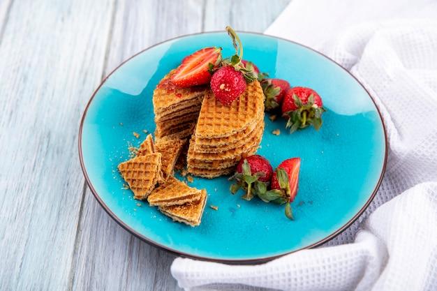Vista laterale di biscotti waffle e fragole nel piatto su legno