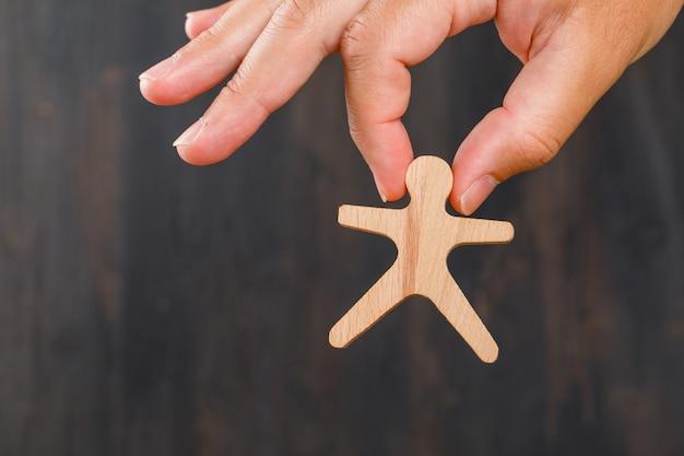 Vista laterale di concetto del pubblico e di affari. mano che tiene il modello umano in legno.