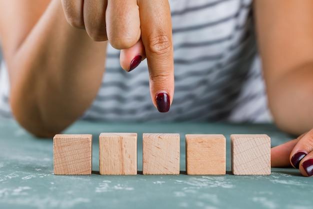 Vista laterale di concetto dell'obiettivo di affari. donna che mostra cubo di legno.