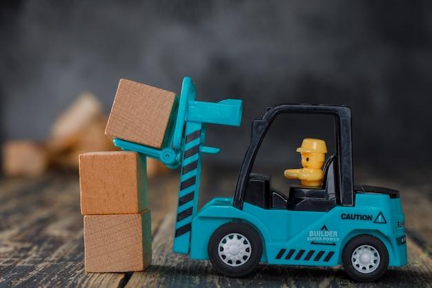 Vista laterale di concetto di pianificazione aziendale. carrello elevatore che impila i blocchi di legno.