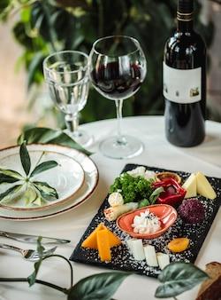 Vista laterale di diversi tipi di formaggi sul piatto bianco sul tavolo