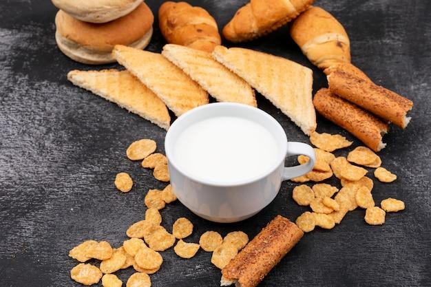 Vista laterale di diversi tipi di pane come cracker, toast, cornetti e latte su superficie nera orizzontale