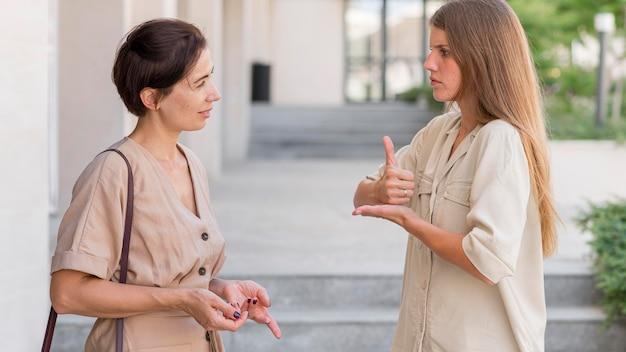 Vista laterale di due amiche all'aperto conversando attraverso il linguaggio dei segni