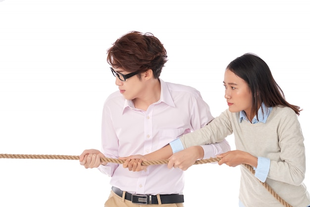 Vista laterale di due asiatici che giocano al tiro alla fune