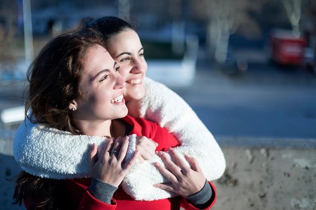 Vista laterale di due donne felici che abbracciano e distoglie lo sguardo