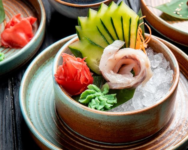 Vista laterale di filetti di aringhe marinate con cetrioli a fette zenzero e salsa wasabi su cubetti di ghiaccio in un piatto sul tavolo