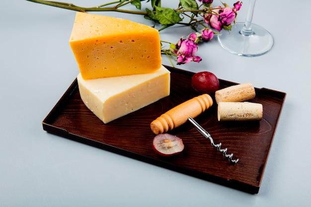 Vista laterale di formaggi come cheddar e parmigiano con tappi d'uva e cavatappi sul tagliere e fiori su bianco
