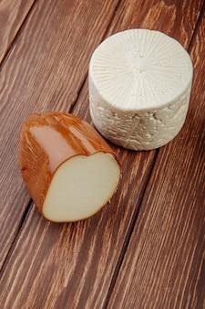 Vista laterale di formaggio affumicato con formaggio di capra sulla tavola rustica di legno