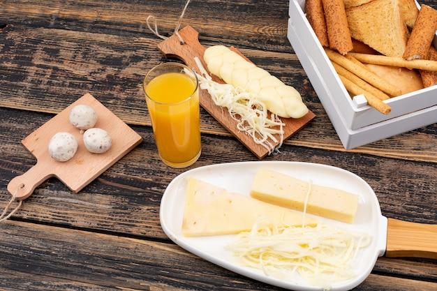 Vista laterale di formaggio con toast, crackers e succo su superficie di legno scuro orizzontale