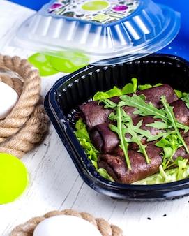 Vista laterale di frittelle nere con urugula in una scatola di consegna sul tavolo