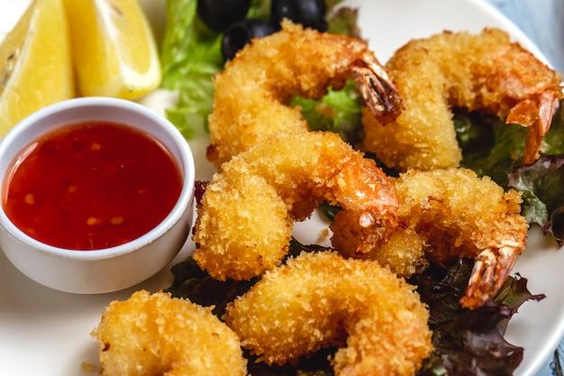 Vista laterale di gamberi tempura con salsa di peperoncino dolce fetta di limone e olive nere su un piatto