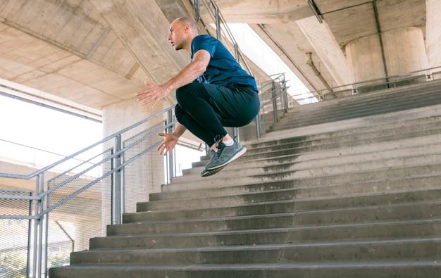 Vista laterale di giovane atleta maschio attivo che salta sopra la scala