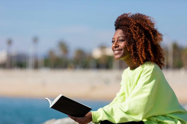 Vista laterale di giovane donna afro riccia che si siede su un frangiflutti che tiene un libro mentre sorridendo e distogliendo lo sguardo all'aperto