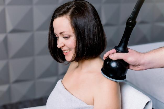 Vista laterale di giovane donna sorridente che ottiene massaggio elettrico sulle suoi spalle e collo nella stazione termale. cosmetologia hardware, attrezzatura per massaggi professionale.