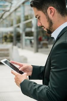 Vista laterale di giovane uomo d'affari bello che per mezzo dello smart phone contro il contesto della sfuocatura