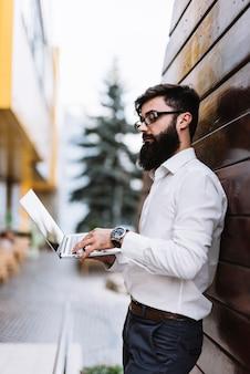 Vista laterale di giovane uomo d'affari che utilizza computer portatile all'aperto