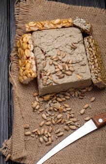 Vista laterale di halva gustoso con barrette di miele con arachidi e semi di girasole su tela di sacco