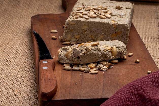 Vista laterale di halva gustoso con un coltello e semi di girasole su una tavola di legno
