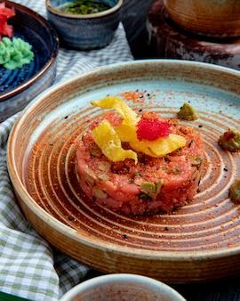 Vista laterale di insalata di salmone con avocado e salsa wasabi su un piatto su tessuto plaid
