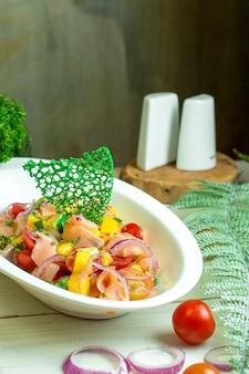 Vista laterale di insalata di salmone con verdure e cipolla in ciotola