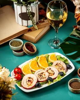 Vista laterale di involtini di pollo ripieni con verdure ed erbe servita con fettine di arancia e pomodorini sul piatto