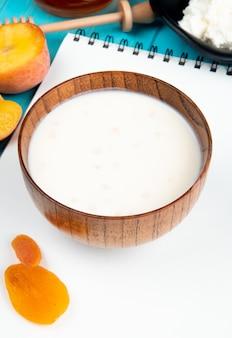 Vista laterale di latte in una ciotola di legno su uno sketchbook e pesche mature fresche delle albicocche secche sul blu