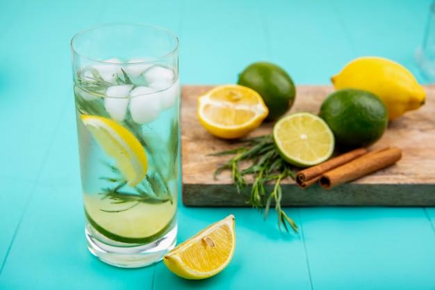 Vista laterale di limoni colorati su una tavola di cucina in legno con bastoncini di cannella con un bicchiere di acqua estiva sulla superficie del blu