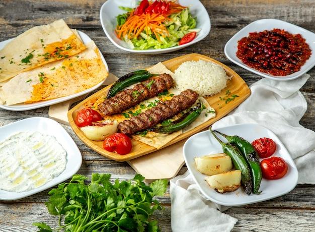 Vista laterale di lula kebab pepe pomodoro cipolla verdi ricotta
