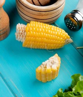 Vista laterale di mais tagliato con sale di lattuga sul tavolo blu