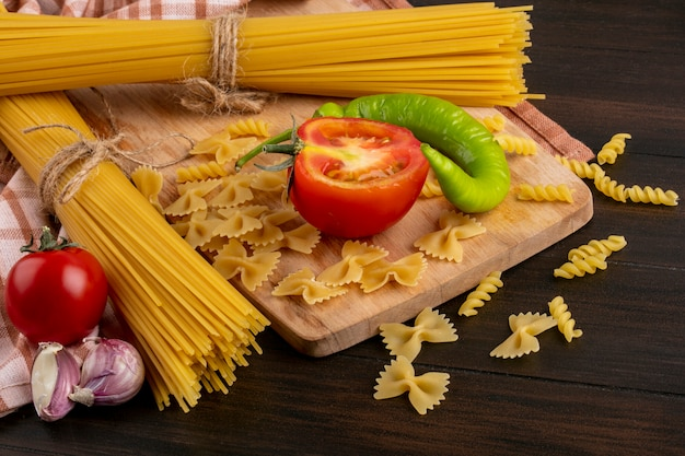 Vista laterale di mazzi di pasta cruda con aglio e pasta con pomodori e peperoncino su una tavola su una superficie di legno